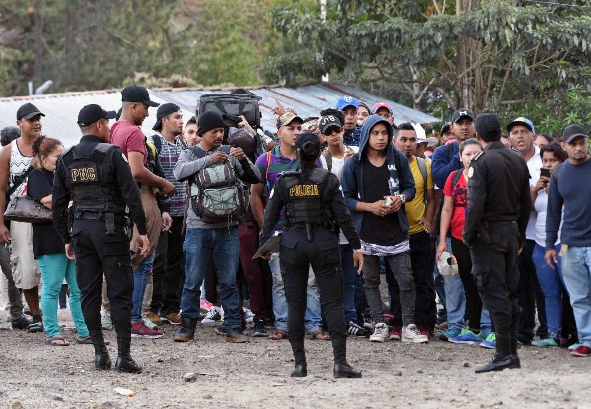 Migrantes hablan con miembros de la Policía de Guatemala después de romper un cordón policial hondureño y cruzar la frontera Honduras-Guatemala en Agua Caliente. Foto: AFP