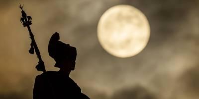 La superluna se eleva por encima de la estatua de Britannia en Hull Guildhall, antes del Eclipse Lunar, en Hull, Inglaterra, el domingo 20 de enero de 2019. (Danny Lawson / vía AP)