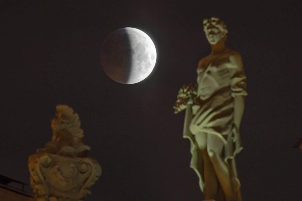 El eclipse lunar progresa detrás de las estatuas en el techo del Museo Estatal del Hermitage en San Petersburgo, Rusia, el lunes 21 de enero de 2019. (Foto AP / Dmitri Lovetsky)