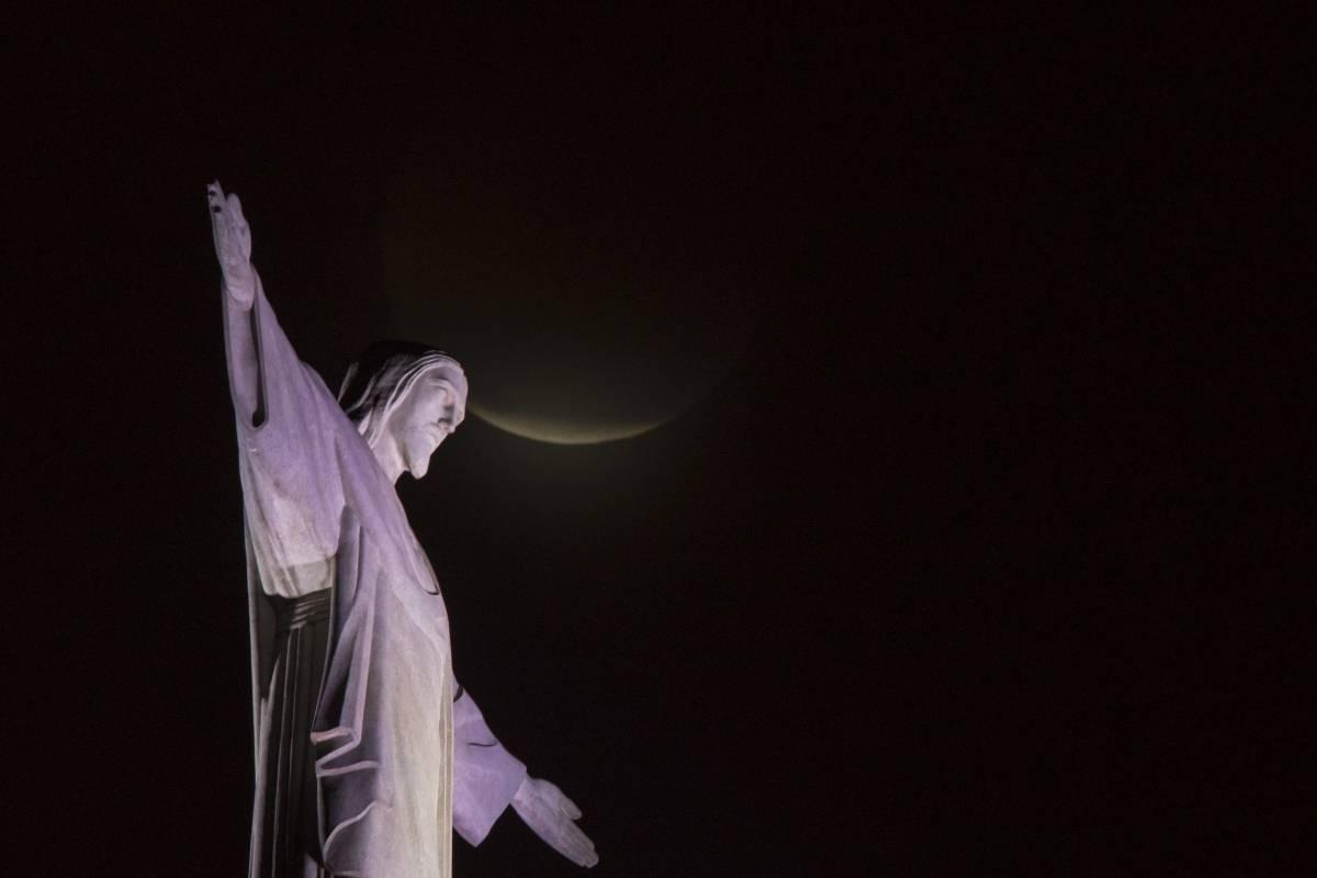 Una luna de sangre se eleva sobre la estatua del Cristo Redentor durante el eclipse lunar en Río de Janeiro, Brasil, el lunes 21 de enero de 2019. (Foto AP / Leo Correa)