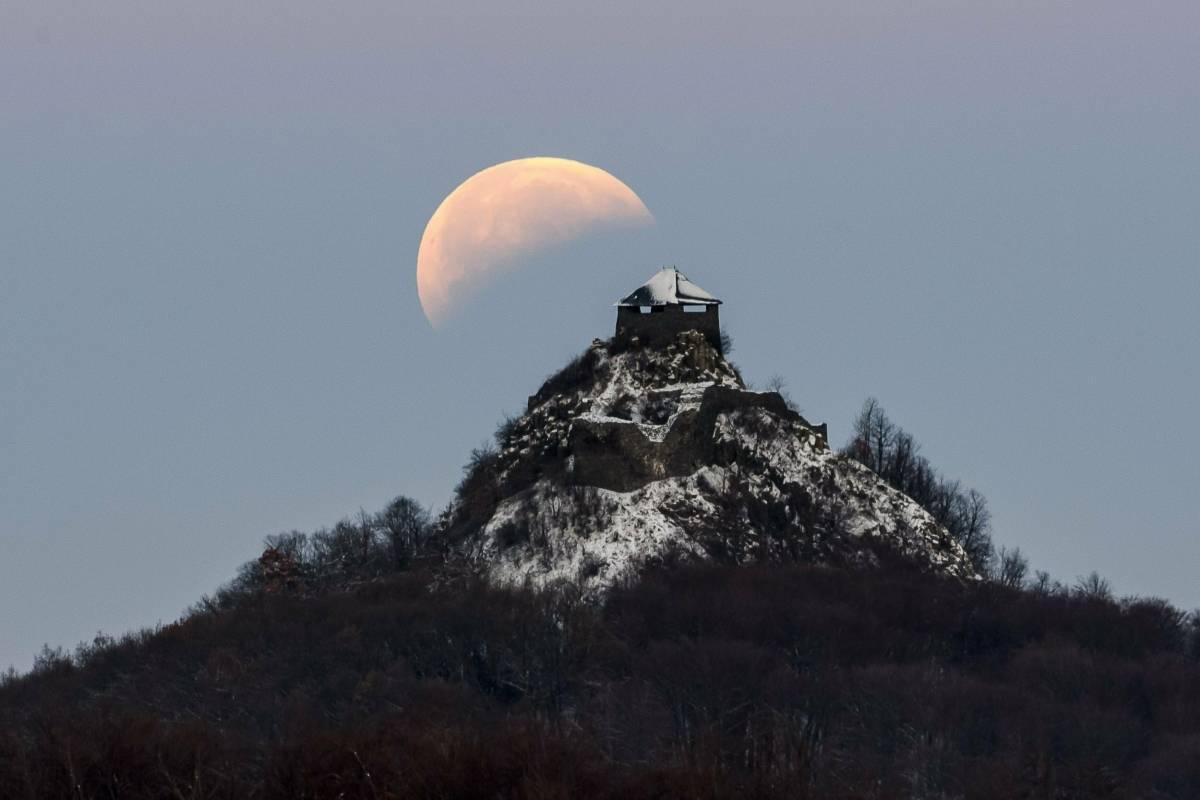 La luna completamente a la sombra de la Tierra se ve sobre el castillo de Salgo durante el eclipse lunar total cerca de Salgotarjan, a 109 km al noreste de Budapest, Hungría, el lunes, 21 de enero de 2019. (Peter Komka / MTI vía AP)