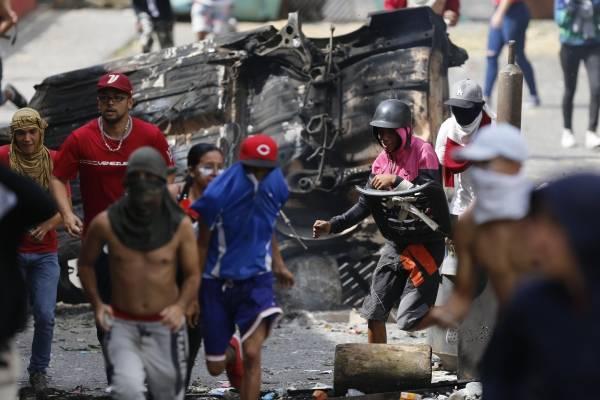 Manifestantes antigubernamentales chocan con las fuerzas de seguridad al mostrar su apoyo a un motín de una unidad de la Guardia Nacional en el barrio de Cotiza en Caracas, Venezuela, el lunes 21 de enero de 2019. (Foto AP / Fernando Llano)