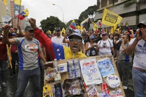 Un opositor sostiene un cartón con bolsas de productos básicos y sus precios durante una protesta contra el presidente venezolano Nicolás Maduro en Caracas, el miércoles 23 de enero de 2019.