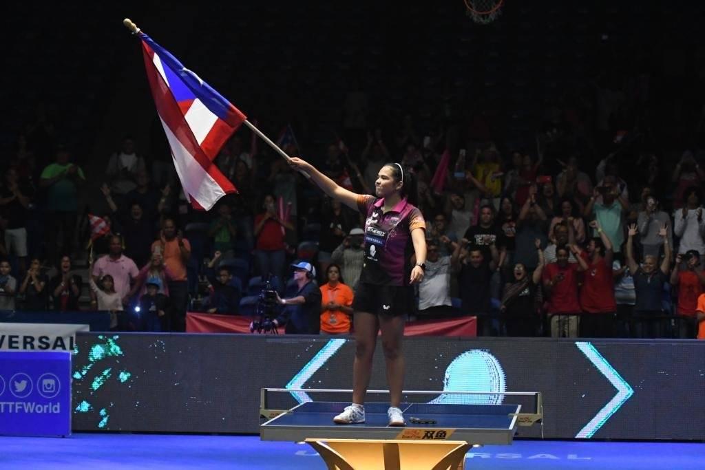 Foto: En cima de la mesa, Adriana Díaz ondea una bandera de Puerto Rico para celebrar el campeonato de la Copa ITTF Panamericana 2019 Dennis A. Jones/Metro PR