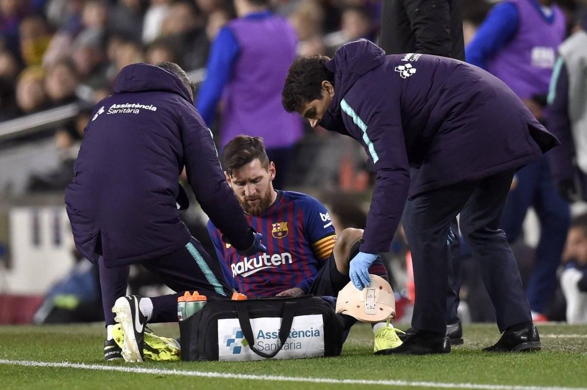 Lionel Messi es atendido por el cuerpo médico del Barcelona en el empate ante el Valencia del sábado pasado por liga española. / Getty Images
