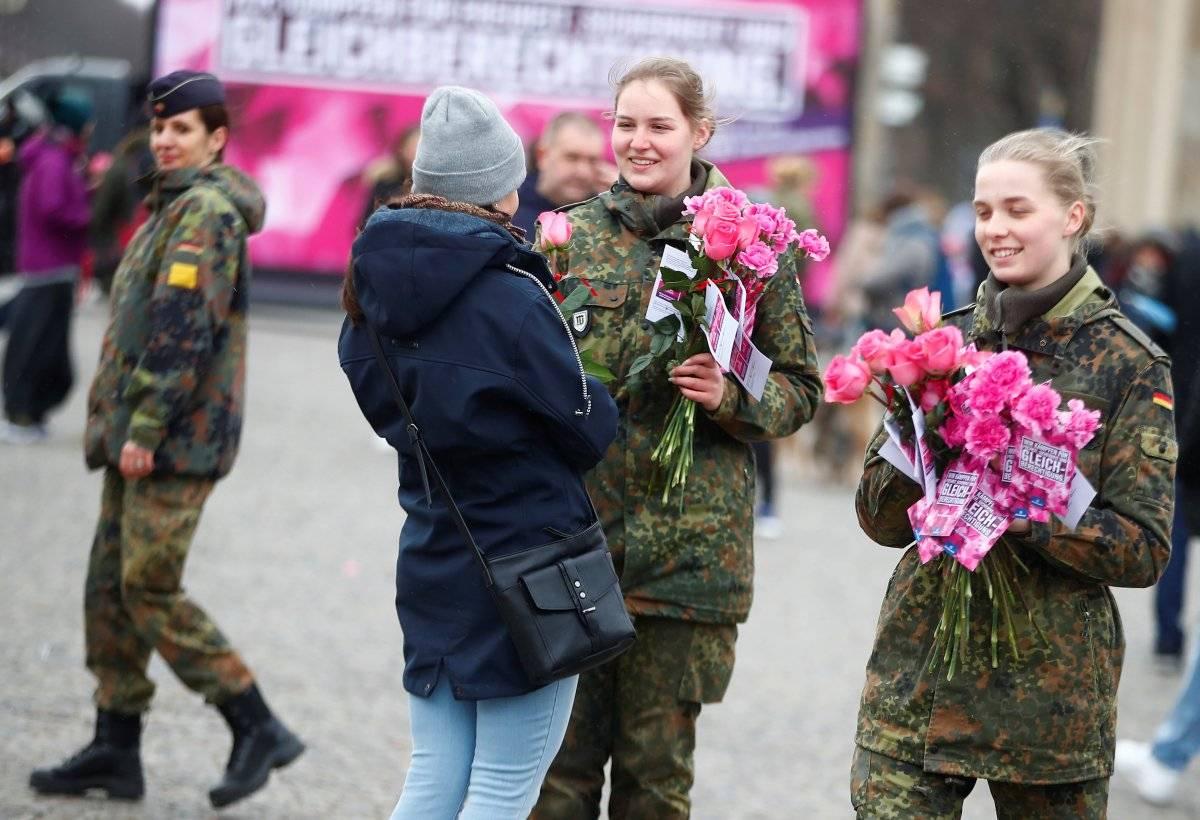 Soldadas entregam flores a mulheres em Berlim, Alemanha REUTERS/Hannibal Hanschke