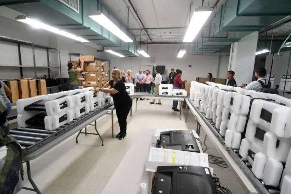 Empleados de la CEE trabajan en la fase uno y dos del proceso de mantenimiento de las máquinas de escrutinio electrónico. / Foto: Dennis Jones