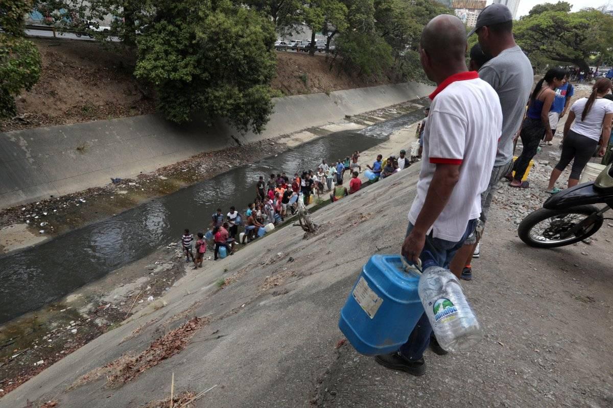 Caraqueños recogen agua en el Río Guaire debido a la escasez por apagón en Venezuela