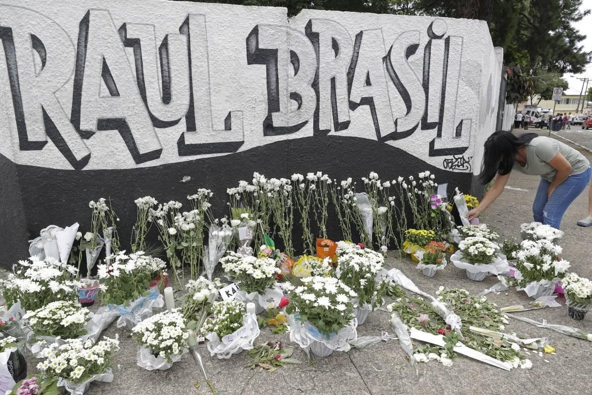 Una mujer deja unas flores un día después de un tiroteo en la escuela pública Raul Brasil, en Suzano, Brasil, el jueves 14 de marzo de 2019. (AP Foto/Andre Penner)