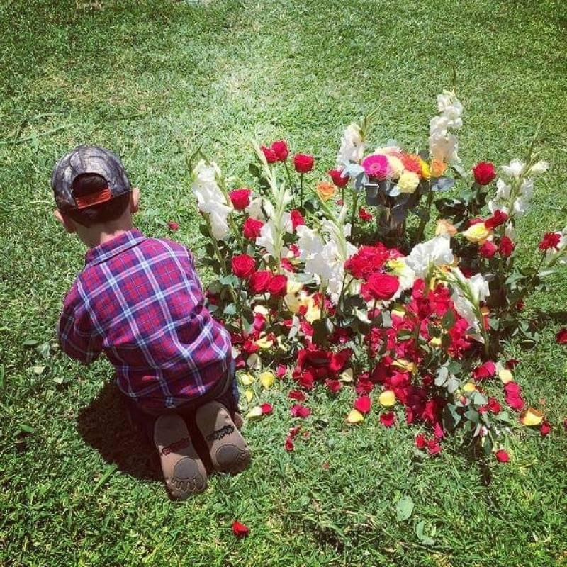 El hijo de Mitzie Sánchez en el cementerio enflorando su tumba. Foto: Cortesía