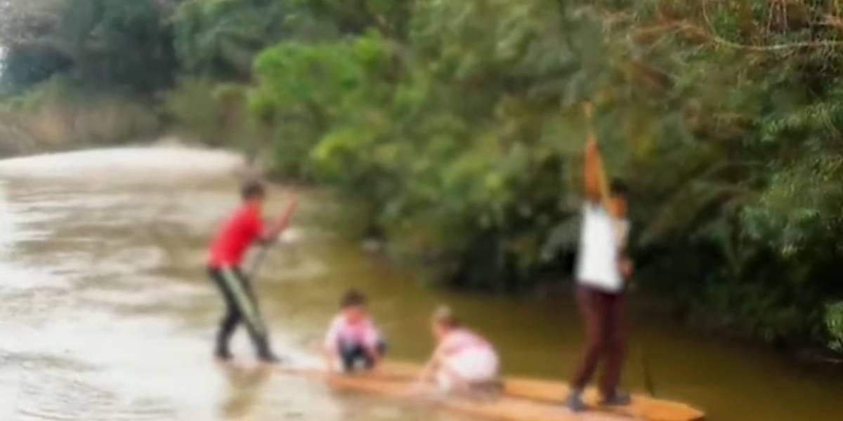 Niños atraviesan en balsa un río con caimanes para llegar al colegio
