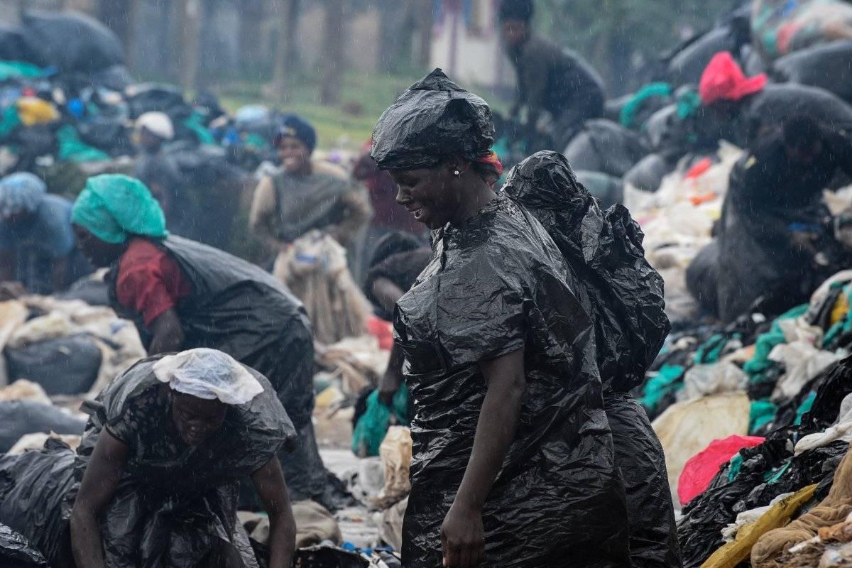 UGANDA, Una foto tomada el 2 de junio de 2018 en Kampala, Uganda, muestra a mujeres limpiando bolsas de plástico para venderlas a una fábrica que las recicla en utensilios de plástico caseros como lavabos, platos y vasos. AFP