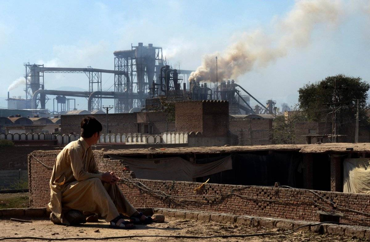 PAKISTAN, Esta fotografía tomada el 25 de febrero de 2017, muestra a un trabajador pakistaní observando humo saliendo de las fábricas en las afueras de la ciudad noroeste de Peshawar. AFP