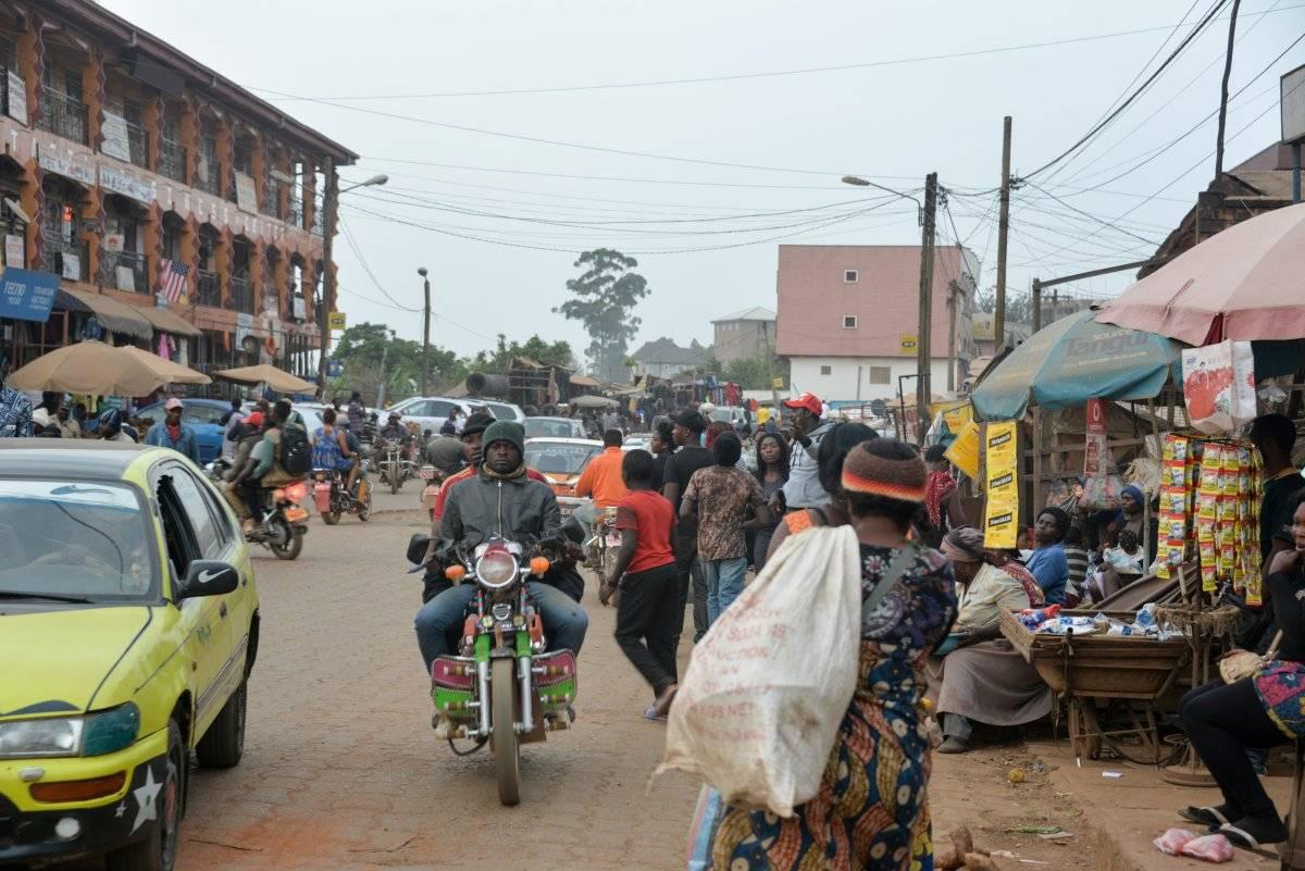 La gente camina en el mercado de alimentos, Cameroon. AFP