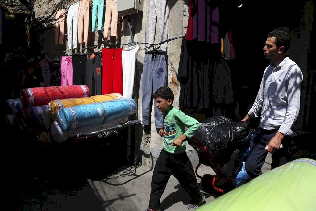 Un joven trabajador jala su mercancía en el principal bazar del Teherán, Irán. Foto: AP