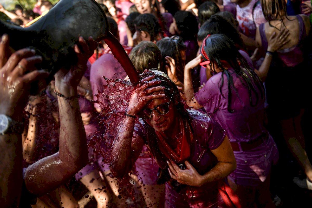Foto: Una mujer es cubierta con vino tinto durante la festividad de la Batalla del Vino, en el municipio de Haro, en el norte de España, el sábado 29 de junio de 2019 AP