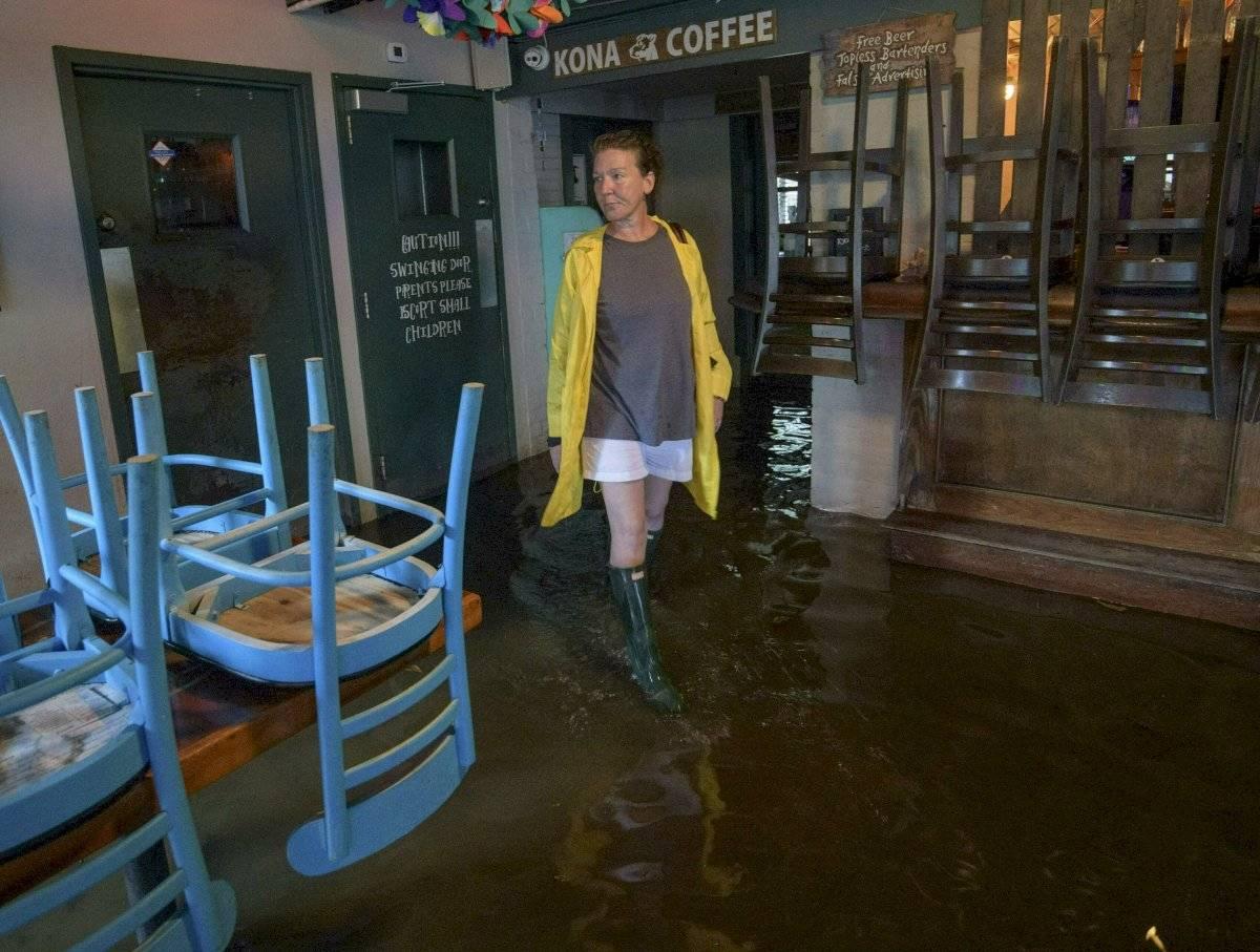 Aimee Cutter, camina en el interior de su restaurante, Beach House, inundado por aguas crecidas del cercano lago Pontchartrain en Mandeville, Luisiana, antes de que tocara tierra el vórtice del huracán Barry, la mañana del sábado 13 de julio de 2019 (Foto AP/Matthew Hinton)