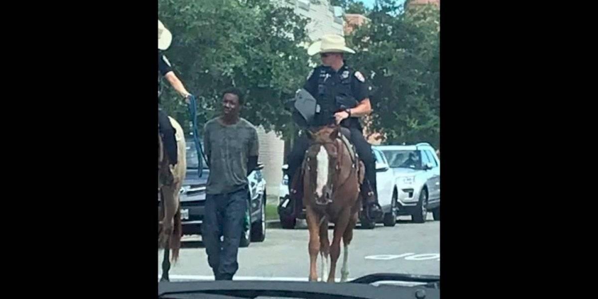 Policías a caballo hacen caminar a hombre negro amarrado de una soga