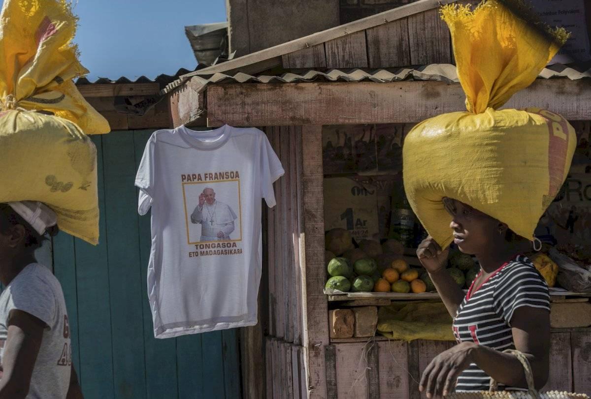 Mujeres con bolsas en sus cabezas pasan por un puesto que vende camisetas del Papa Francisco conmemorando su visita a Madagascar