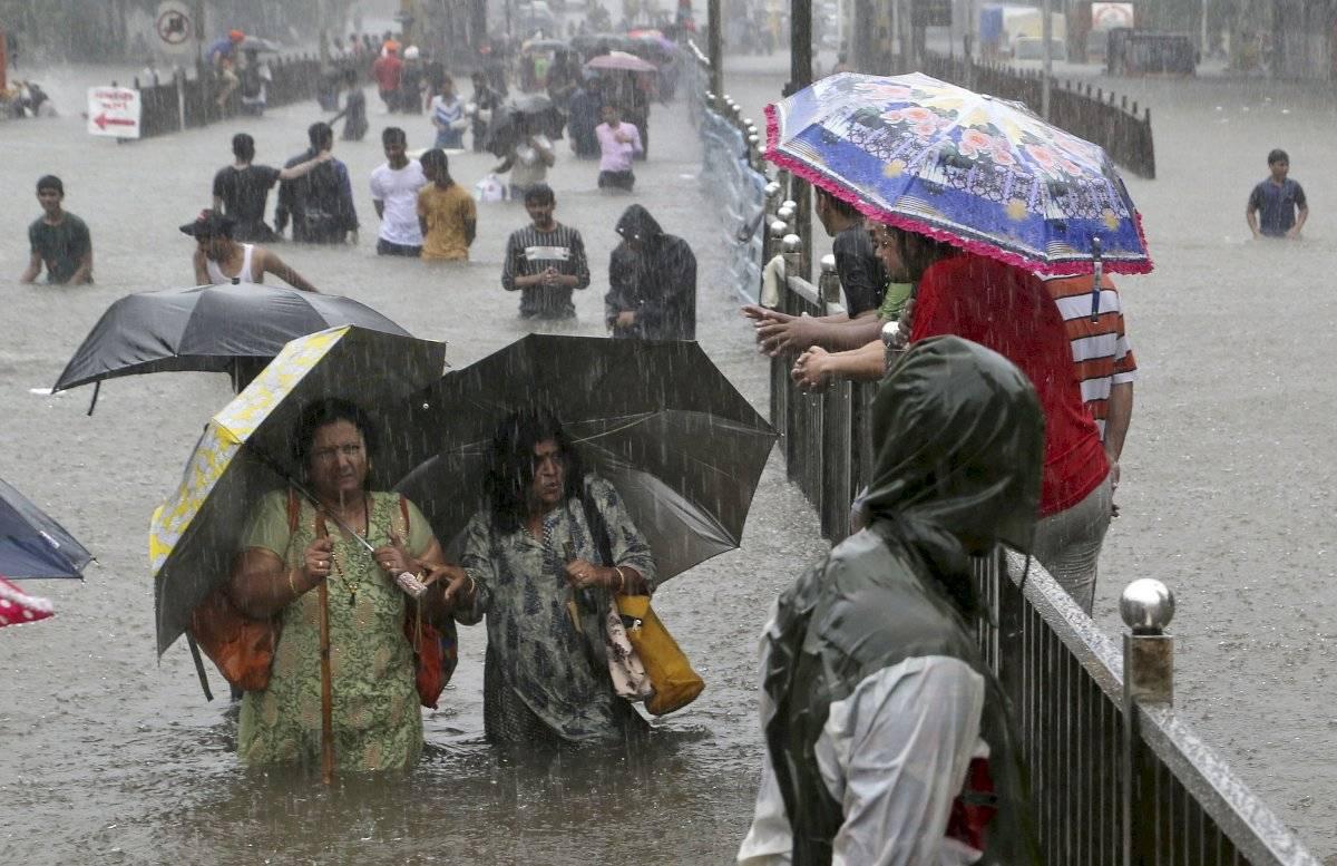 La gente navega a través de una calle inundada mientras llueve en Mumbai, India, el miércoles 4 de septiembre de 2019. La lluvia incesante ha provocado inundaciones en muchas partes de la ciudad, interrumpiendo el movimiento del tráfico y la vida cotidian