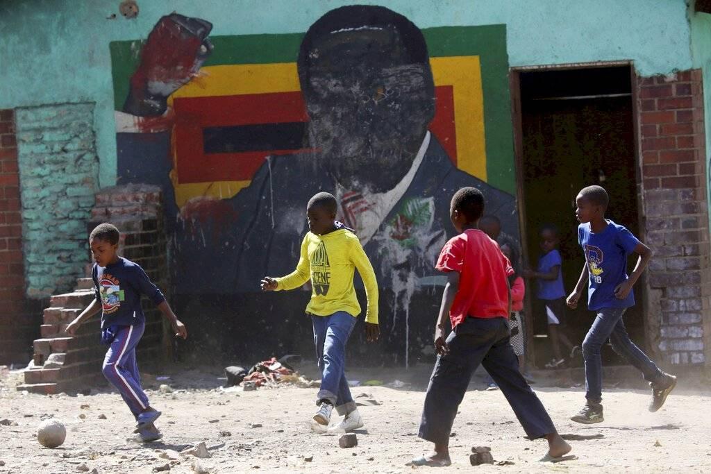 Niños juegan fútbol junto a un retrato desfigurado del ex presidente zimbabuense Robert Mugabe en Harare, el viernes 6 de septiembre de 2019, día en que falleció a los 95 años.