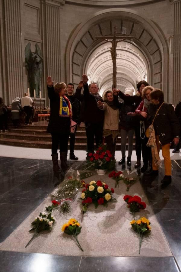 Los visitantes posan para fotos haciendo un saludo fascista por la tumba del dictador Francisco Franco dentro del mausoleo en el