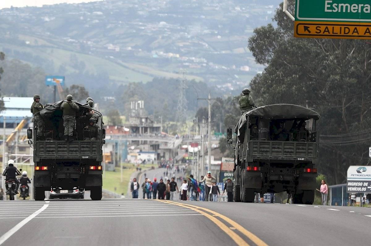 Camiones con militares transitan una calle ocupada por manifestantes este lunes, en Quito (Ecuador). EFE