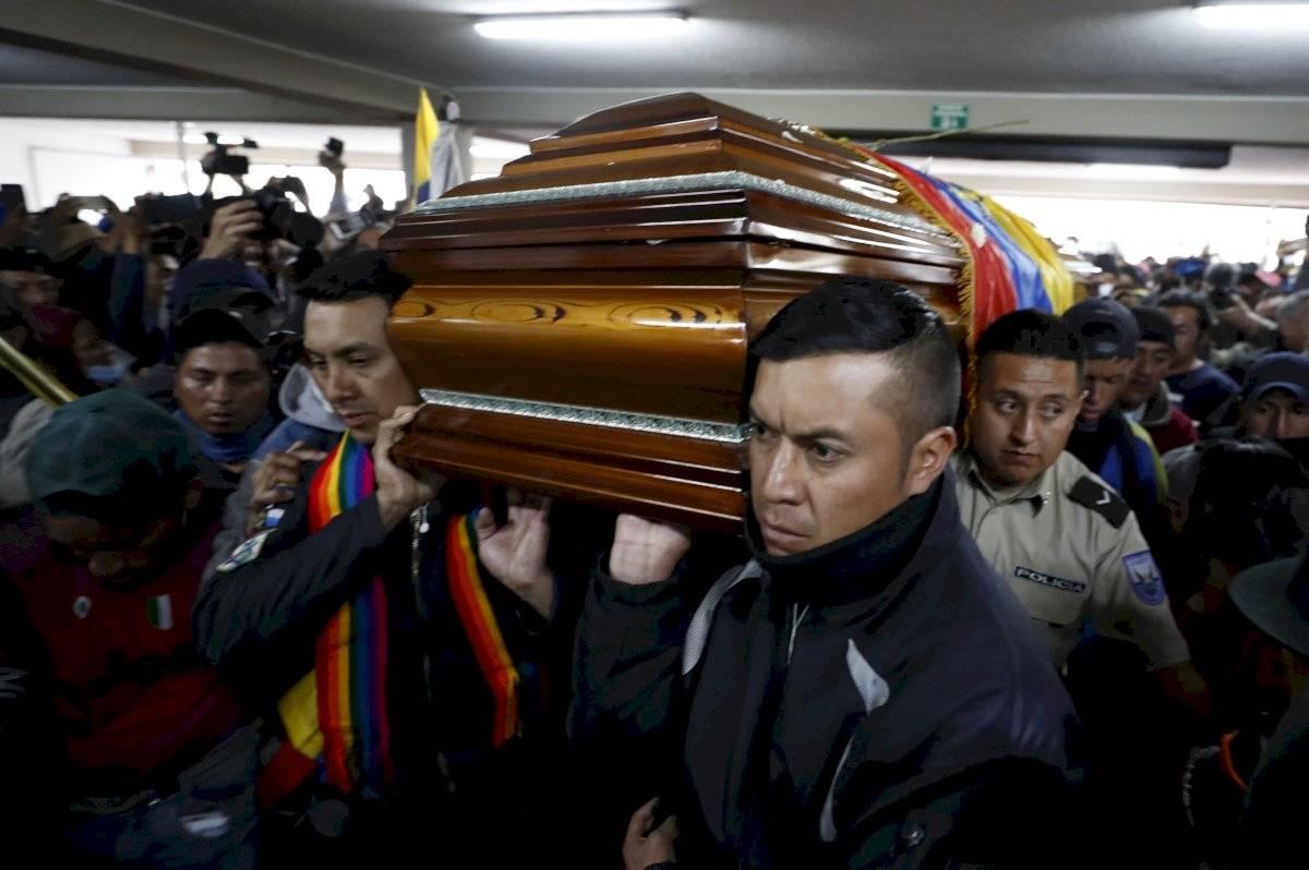 Policías cargan los féretros de las personas que murieron en las manifestaciones EFE