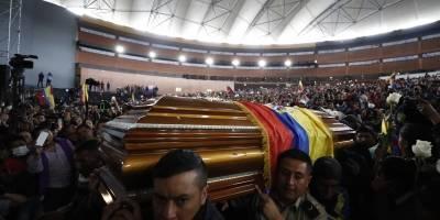 Policías cargan los féretros de las personas que murieron en las manifestaciones