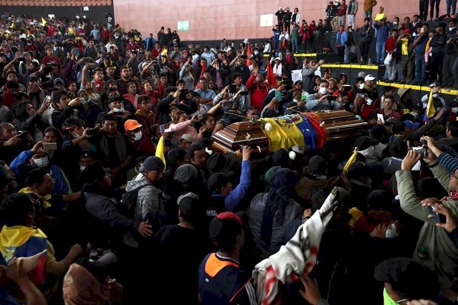 Policías retenidos cargan el féretro del manifestante indígena muerto en choques con la Policía