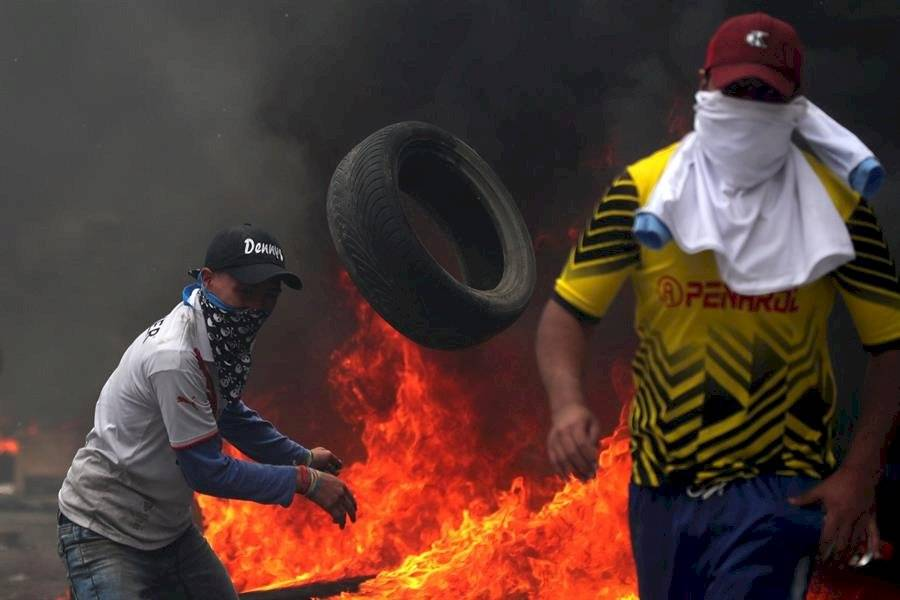 Manifestantes se cubren tras varias barricadas mientras enfrentan a la policía cuando se cumplen 10 días de protestas contra el Gobierno EFE