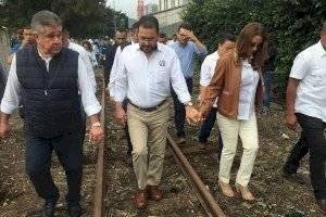 Jimmy Morales y su esposa caminan por la vía férrea