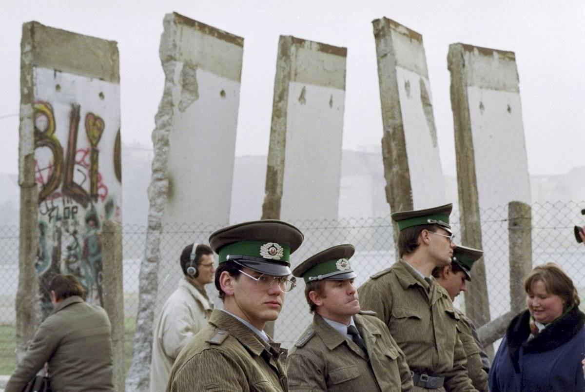 En esta imagen de archivo, tomada el 13 de noviembre de 1989, guardas fronterizos de Alemania Oriental hacen guardia ante fragmentos del Muro de Berlín que se retiraron para abrir el muro en el paso de la Plaza Potsdamer, en Berlín. Foto: John Gaps III, archivo (AP)