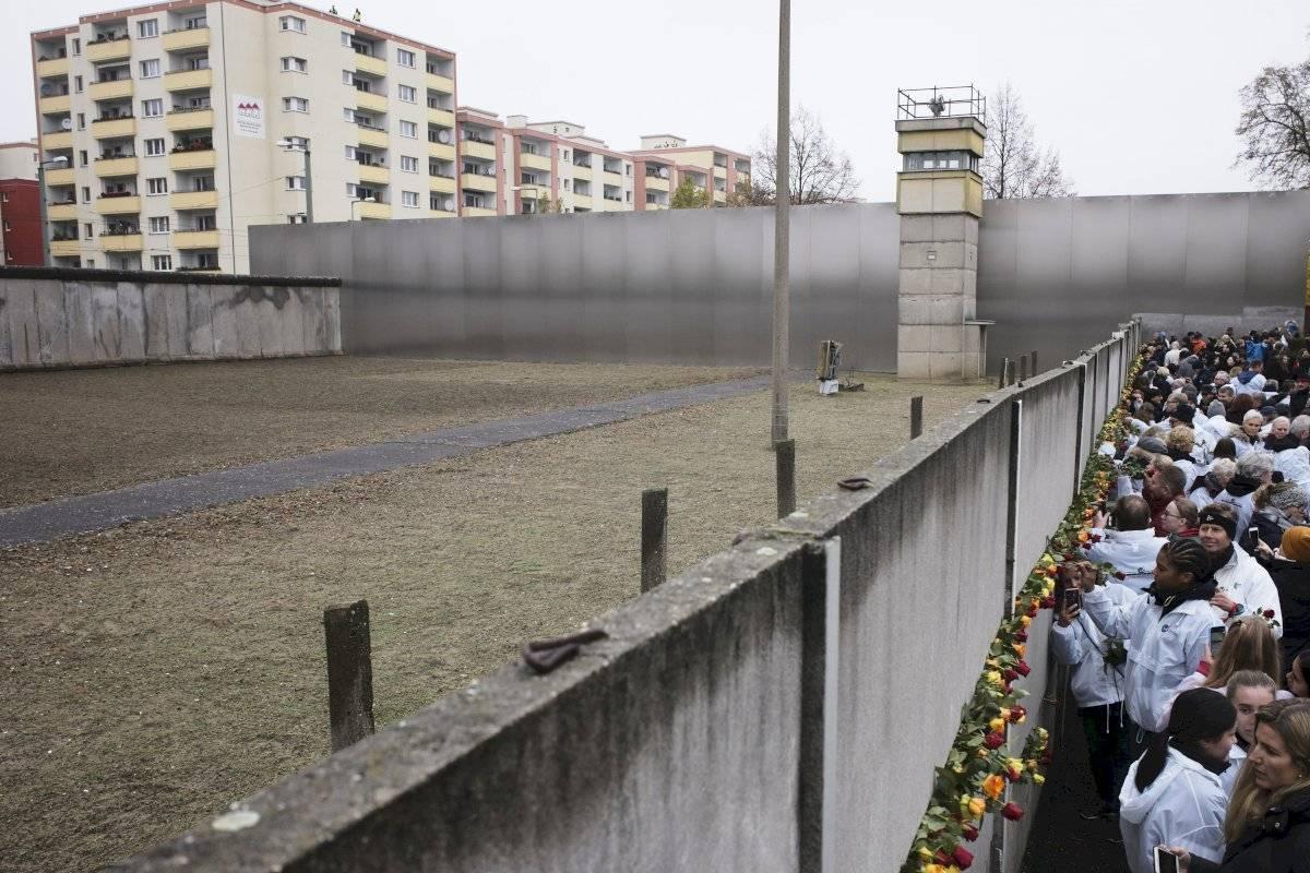 Personas colocan rosas en lo que queda en pie del Muro de Berlín durante una ceremonia para conmemorar el 30 aniversario de la caída del muro en el memorial en Bernauer Strasse en Berlín, el sábado 9 de noviembre de 2019. Foto: Markus Schreiber (AP)