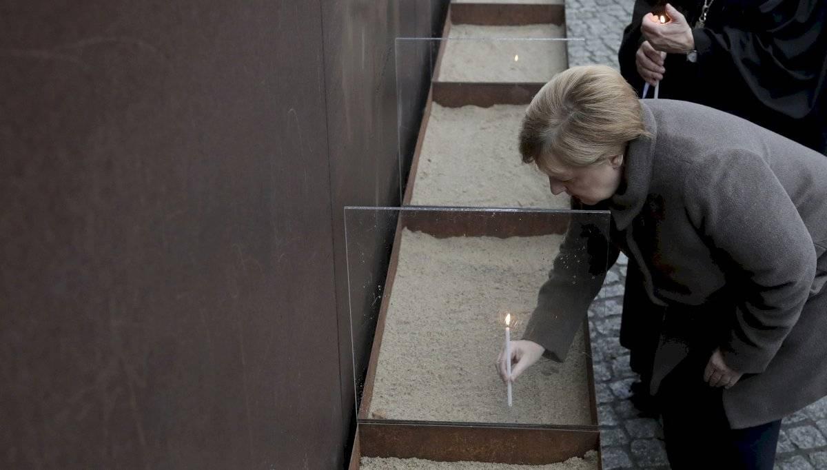 La canciller alemana Angela Merkel coloca una vela en el memorial del Muro de Berlín después de un servicio para conmemorar el 30 aniversario de la caída del muro en Berlín, el sábado 9 de noviembre de 2019. Foto: Michael Sohn (AP)