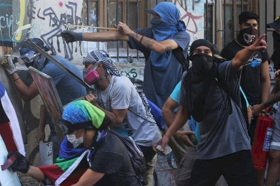 Un grupo de manifestantes se enfrenta a la policía antidisturbios hoy martes, en Santiago de Chile. EFE