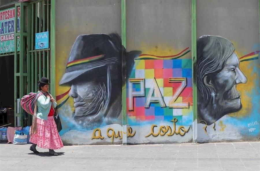 Ciudadanos bolivianas frente a una pared con grafitis alusivos a las pasadas protestas EFE