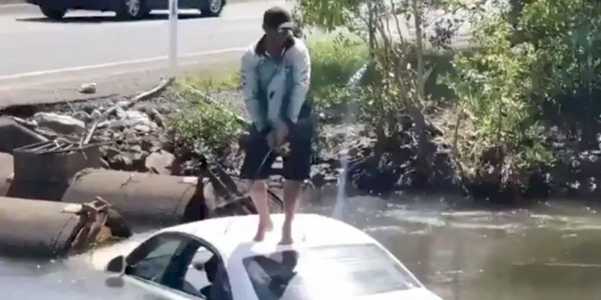 Hombre usa auto semihundido en arroyo de cocodrilos como lancha de pescar