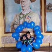 Cachorros de los scouts frente al retrato de lord Robert Baden-Powell.