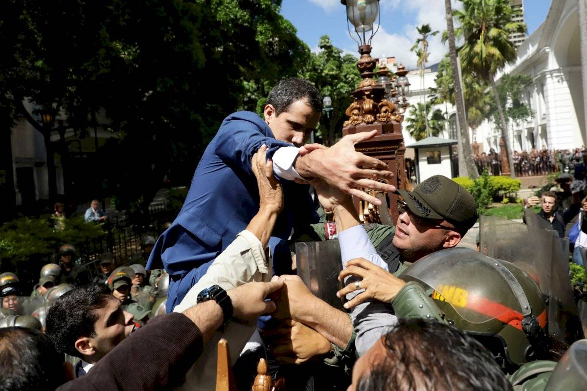 l líder opositor venezolano Juan Guaidó trepa una reja en un intento por ingresar a la sede de la Asamblea Nacional