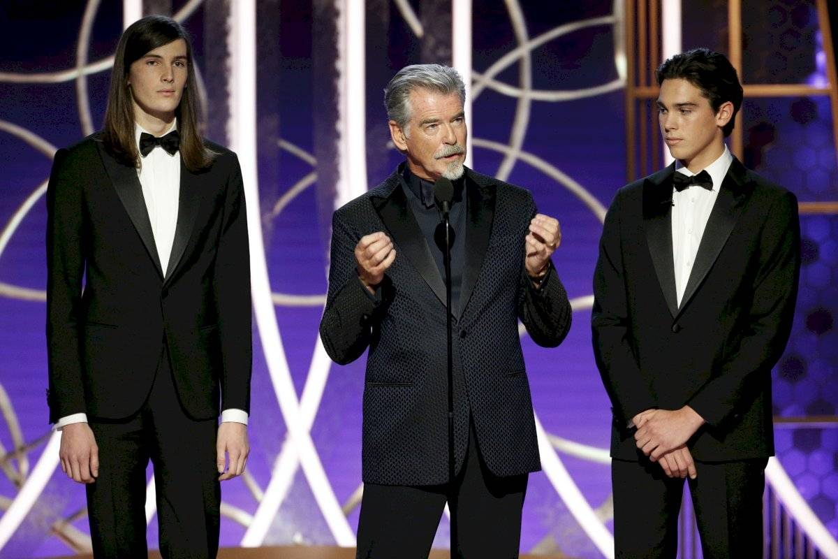 En esta imagen difundida por NBC, Pierce Brosnan, con sus hijos Dylan, a la izquierda, y Paris, habla en la ceremonia de los Globos de Oro el domingo 5 de enero del 2020 en Beverly Hills, California. (Paul Drinkwater/NBC via AP)