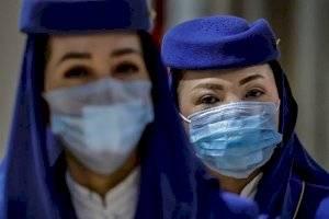 Los asistentes de vuelo son vistos usando máscaras faciales, a medida que crece el temor público sobre el coronavirus Wuhan de China