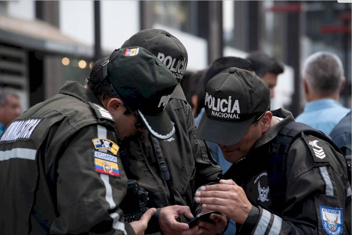 Policías reunidos observando imágenes de la cámara del ECU 911 que registró el momento del asalto a Mariana Granja Oscar Ayo