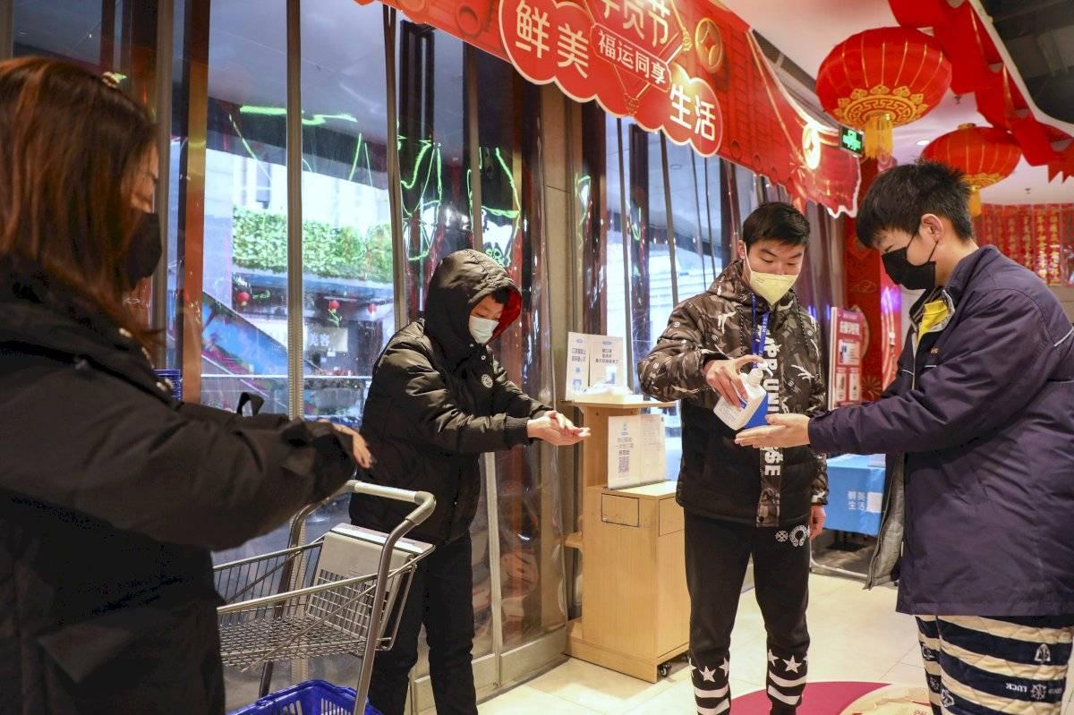 Entrada de mercado en Wuhan, y en la entrada un trabajador dando gel antibacterial a clientes.