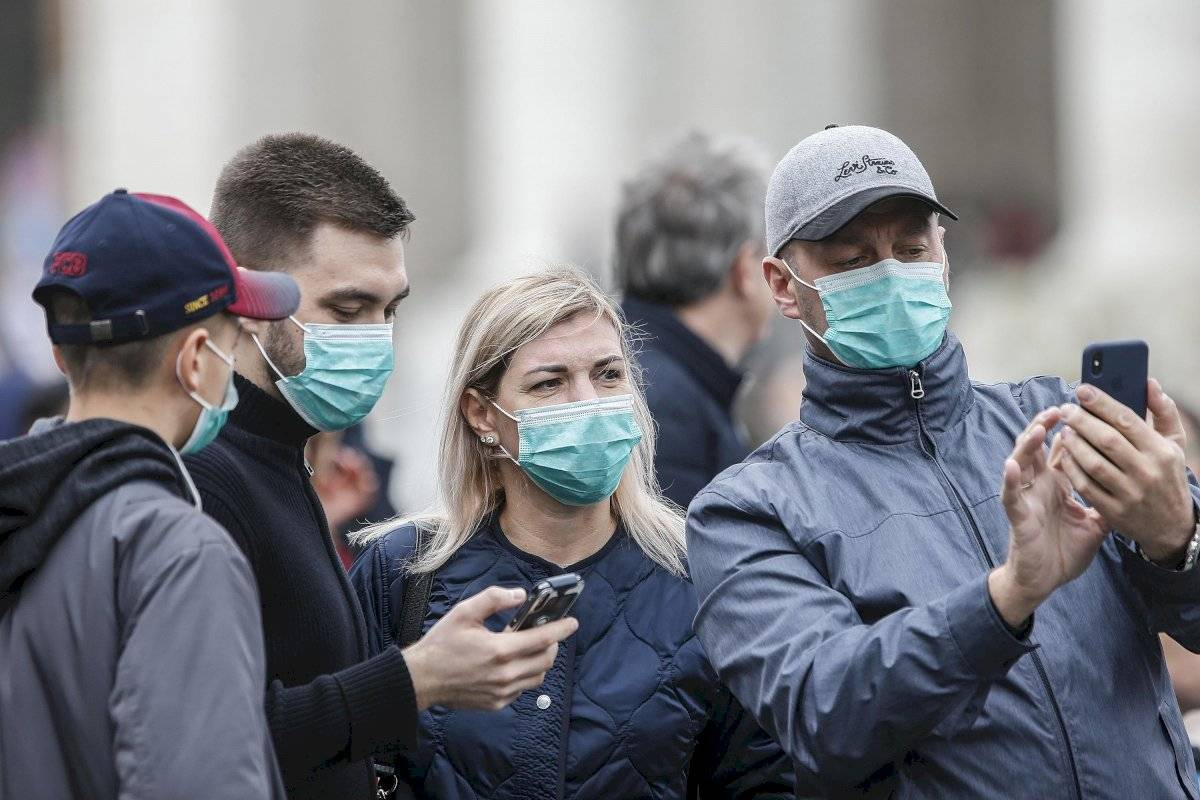 Varios asistentes llevan mascarillas para protegerse del coronavirus mientras asisten a la oración del Angelus, oficiada por el papa Francisco, en la plaza de San Pedro del Vaticano