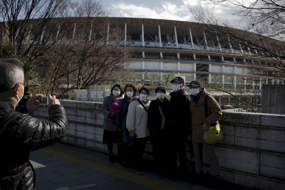 Turistas con mascarillas posan para un foto delante del Nuevo Estadio Nacional, donde se celebrarán las ceremonias de inauguración y clausura de los Juegos Olímpicos de Tokio 2020, el 23 de febrero de 2020, en Tokio.