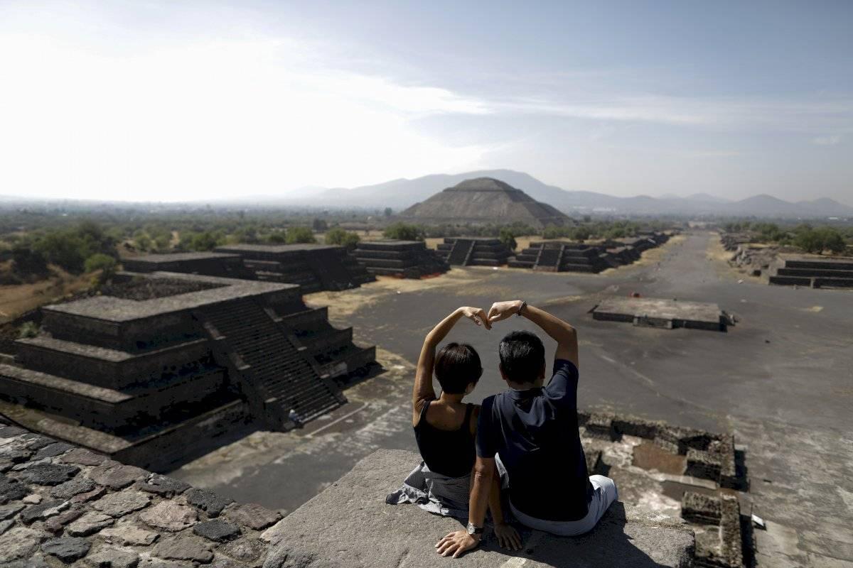 Los turistas sudcoreanos Myung Hee Lee, izquierda, y Byung Ho Im, forman un corazón con las manos mientras posan para una foto en el tope de la Pirámide de la Luna en Teotihuacán, México.