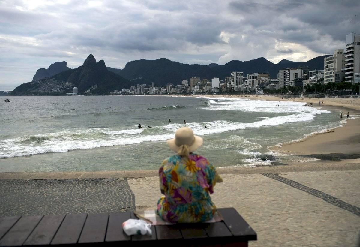 Una mujer mira la playa Arpoador, virtualmente vacía, en Río de Janeiro, Brasil.