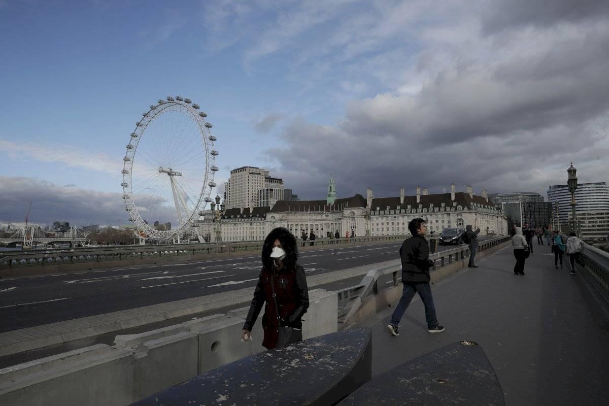 Una mujer con una máscara camina sobre el Puente de Westminster en Londres.