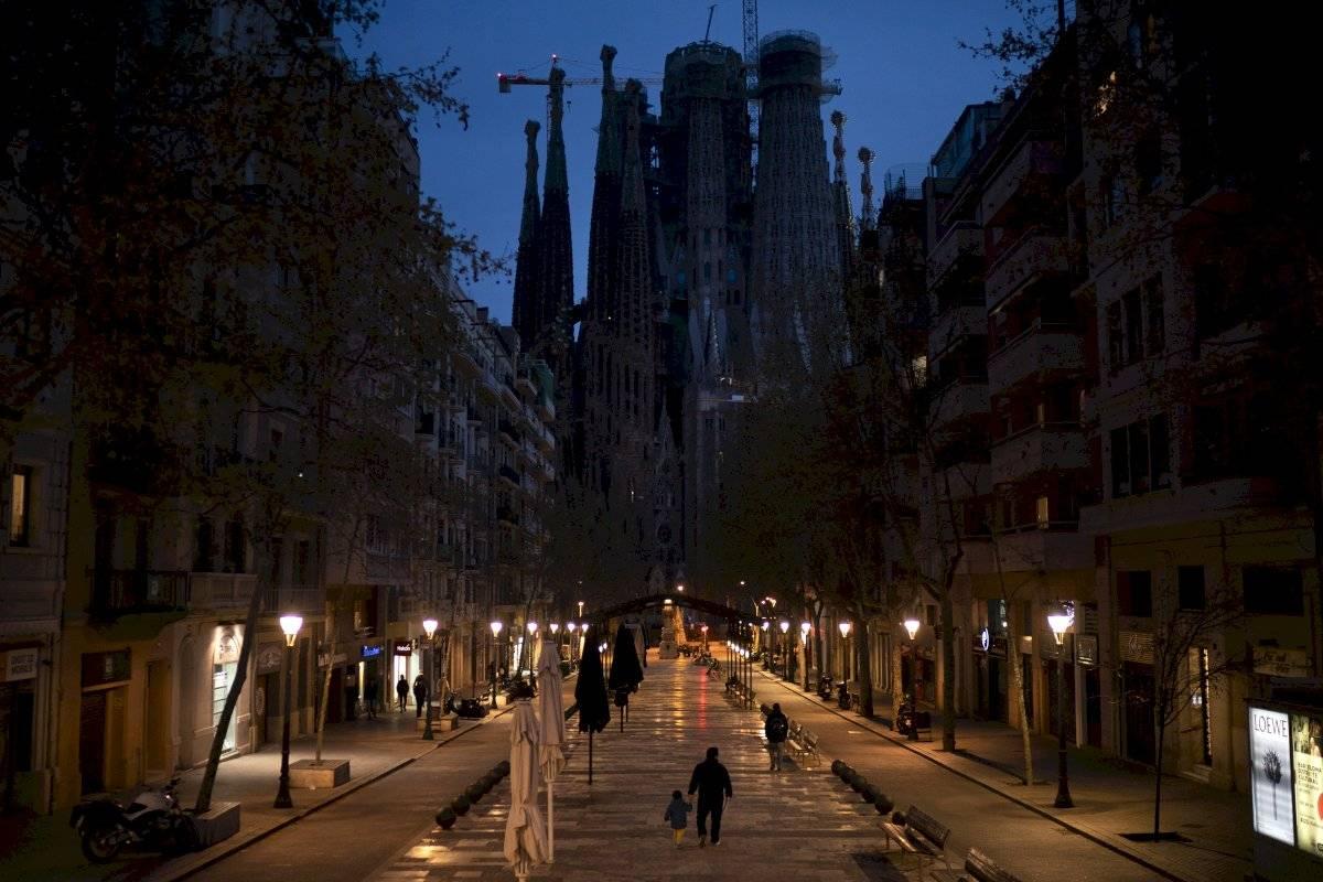Transeúntes caminan junto a tiendas y restaurantes cerca de la Basílica de La Sagrada Familia en Barcelona